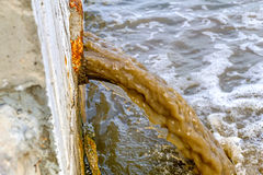 Dirty water discharged into river side view Royalty Free Stock Photo