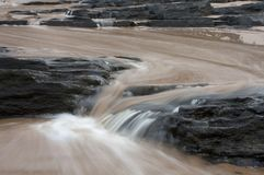 Dirty water flowing from storm water drains into the sea South Africa. Fast flowing water Royalty Free Stock Image
