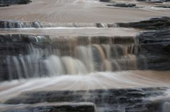 Dirty water flowing from storm water drains into the sea South Africa. Fast flowing water Stock Photo