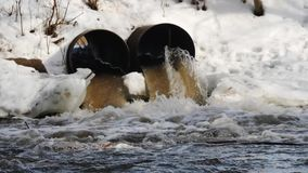 Dirty water flows out of the concrete pipe. Environmental pollution. Drainage channels drained the fluid flow. Spring day