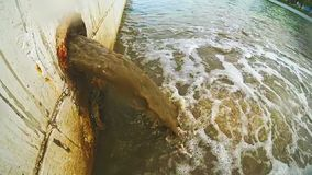 Dirty water flows from a pipe into the city river. The drain carries sewage stock video footage