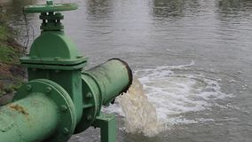 Dirty water flows from a steel pipe Stock Photo