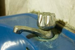 Dirty Water Tap. Old Dirty Never been cleaned Water Tap attached to blue ceramic sink Stock Photo