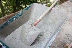 Dirty wheelbarrow containing concrete mix Stock Photos
