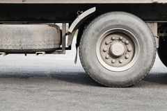Dirty wheels of lorry on asphalt road Stock Images