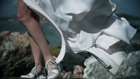 White wedding dress flutters in wind, water drops splash on legs of girl in white dress. Dirty white cloth flutters in wind, water drops splash on legs of girl stock video footage