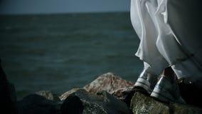 White wedding dress flutters in wind, water drops splash on legs of girl in white dress. Dirty white cloth flutters in wind, water drops splash on legs of girl stock footage