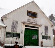 Dirty white multi-storied barn with green barn door and multi-paned windows. 2 lanterns, grimes,snow covered ground and small stock photo