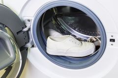Dirty white sneakers in washing machine Stock Images
