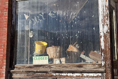 Dirty window in an old closed Dry Goods store royalty free stock photography