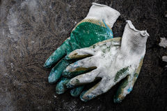Dirty work gloves. Over grey royalty free stock image