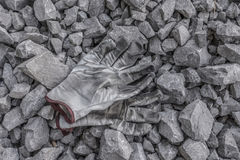 Dirty work. Pair of leather work gloves on rocks royalty free stock images