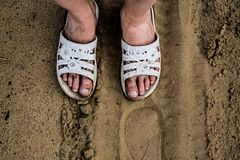 Dirty, working and tired girl`s feet in white dusty Slippers on the background of sand. stock photography