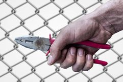 Dirty workman hand hold a plierspincer on barb wire background. Close Royalty Free Stock Photos