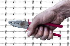 Dirty workman hand hold a plierspincer barb wire background. Close Royalty Free Stock Photos