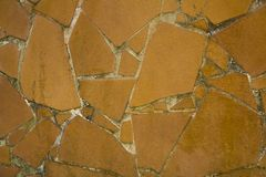 A dirty yellow brown fragments of ceramic tiles in light cement. rough surface texture. Dirty yellow brown fragments of ceramic tiles in light cement. rough royalty free stock photo