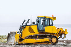 Dirty Yellow bulldozer going left on ground. Dirty Yellow bulldozer in wide angle, powerfull Stock Photos