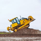 Dirty Yellow bulldozer overcome ground barrier. Going up Stock Photography