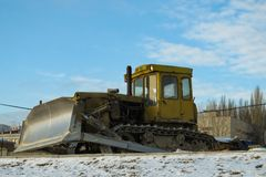 Dirty yellow bulldozer. on the winter road because construction stopped stock photo