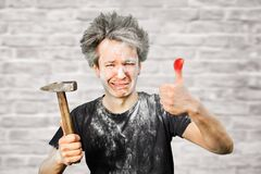 Free Dirty Young Builder Guy Fail Is Hold A Hammer, Hit The Finger On Brick Wall Background At Home During Repairs Royalty Free Stock Photos - 174357508