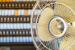 Dirtyand Old Vintage electric fan with rows of Bottles in background. Concept for article royalty free stock photography