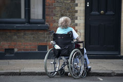 With disabilities in a wheelchair with an oxygen cylinder is waiting in the street Stock Images