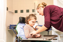 Disability a disabled child in a wheelchair being cared for by a nurse
