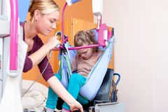 Disabled child being lifted into a wheelchair Stock Photos