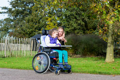 Disabled girl in a wheelchair relaxing outside. A disabled girl in a wheelchair relaxing outside together with a care assistant Royalty Free Stock Photos