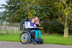 Disabled girl in a wheelchair relaxing outside stock images