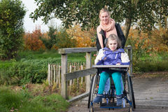 Disabled girl in a wheelchair relaxing outside royalty free stock images