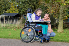 A disabled girl in a wheelchair outside with a care assistant royalty free stock photos