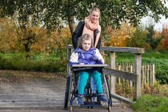 Disabled girl in a wheelchair relaxing outside. A disabled girl in a wheelchair relaxing outside together with a care assistant Stock Photos