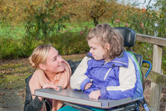 Disabled girl in a wheelchair relaxing outside royalty free stock photography