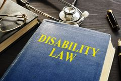 Disability Law book and stethoscope on a desk. Disability Law book and stethoscope on the desk royalty free stock image