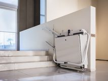 Disability stairs lift facility indoor building Wheelchair elevator stock image