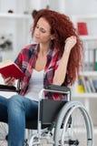Disabilty und junge behinderte Frau des Handikaps auf Rollstuhl liest Buch stockbilder