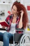 Disabilty und junge behinderte Frau des Handikaps auf Rollstuhl liest Buch stockbild
