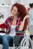Disabilty und junge behinderte Frau des Handikaps auf Rollstuhl liest Buch lizenzfreies stockbild
