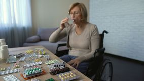 Disable female in wheelchair drinking pills with water, recovery, nursing home. Stock footage stock footage