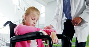 Disable girl sitting on wheel chair talking to doctor. In hospital stock video footage
