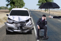 Disable man with broken car. Disabled businessman sitting on wheelchair under umbrella with a broken car on the road Royalty Free Stock Image