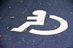 Disable sign on the road. White wheel chair sign on the road for handicap people usage Stock Photo