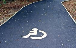 Disable sign on the road. White wheelchair sign on the road for handicap people usage Stock Image