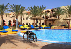 Disable vacations. Disable wheelchair at Egyptian swimming pool Royalty Free Stock Images