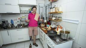 disabled άτομο χωρίς πόδι Καθαρισμός της κουζίνας στοκ εικόνα