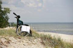 Disabled. Empty wheelchair on the beach Stock Photos