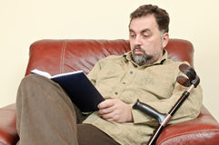 Disabled adult man reading a book Stock Images