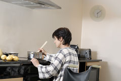 Disabled adult woman in wheelchair cooking dinner Royalty Free Stock Photography