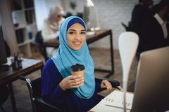 Disabled arab woman in wheelchair working in office. Woman is working on desktop computer and drinking coffee. Disabled arab women in hijab in wheelchair stock photography